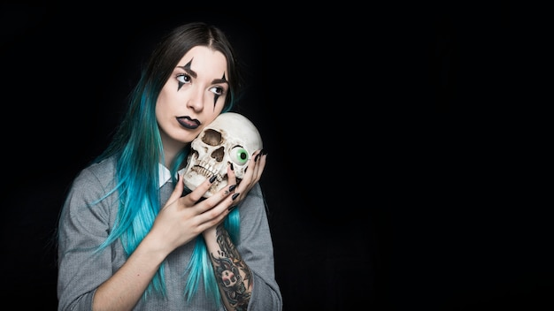 Young female embracingskull with toy eyeball