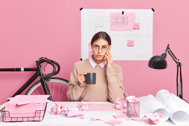 若い女性従業員は、デスクトップでのスマートフォンのポーズを介してコンサルティングを行い、デスクトップでコーヒーのポーズをしわくちゃの紙で囲み、建築家プロジェクトがスタートアップのアイデアを共有する準備をします。生産性