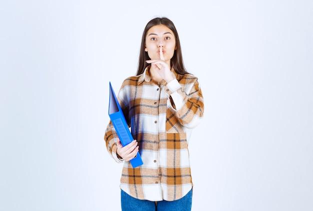 青いホルダーを保持し、沈黙のサインを与える若い女性従業員。