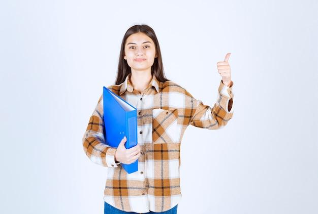 青いホルダーを保持し、親指をあきらめる若い女性従業員。