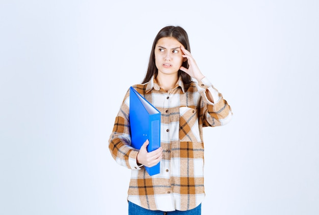 Young female employee holding blue holder and looking somewhere.