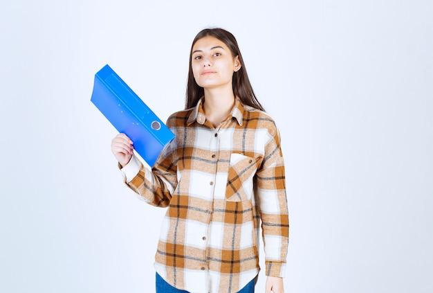 흰 벽에 파란색 홀더를 들고 있는 젊은 여성 직원.