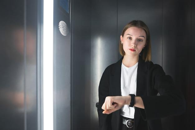 소송에서 젊은 여성 직원은 엘리베이터에서 시간을 확인하고 있습니다.