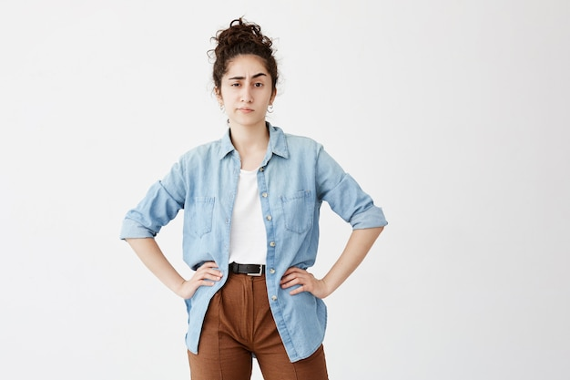 仕事の後家で休む若い女性従業員。白い壁に腰に手を立って、お友達を待っている何気なく待っている服を着て、お団子の暗い巻き毛のかなり学生の女の子