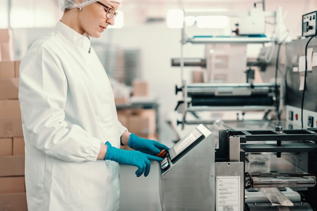 Young female employee in sterile uniform and blue rubber gloves turning on packing machine while standing in food factory.