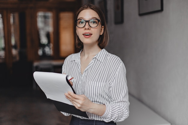 Young female employee in striped blouse holds folder with documents and looks into camera through her glasses.