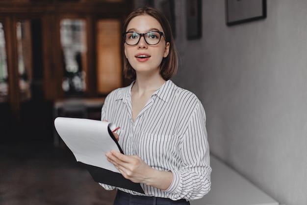 Il giovane impiegato femminile in camicetta a strisce tiene la cartella con i documenti ed esamina la macchina fotografica attraverso i suoi occhiali.