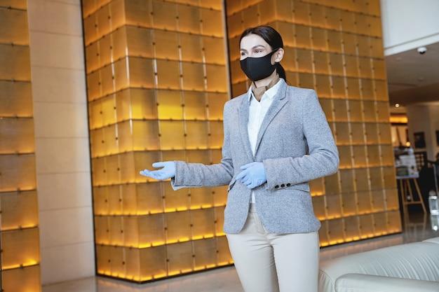 Молодая сотрудница в маске и резиновых перчатках показывает путь к комнатам. баннер веб-сайта