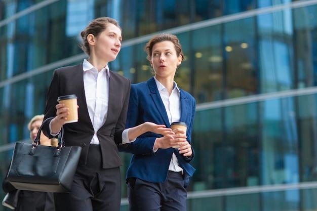 オフィススーツを着て紙のコーヒーカップを持つ若い女性従業員が、ガラスのオフィスビルを通り過ぎて歩いて、話して、プロジェクトについて話し合っています。ローアングル。仕事の休憩や友情の概念