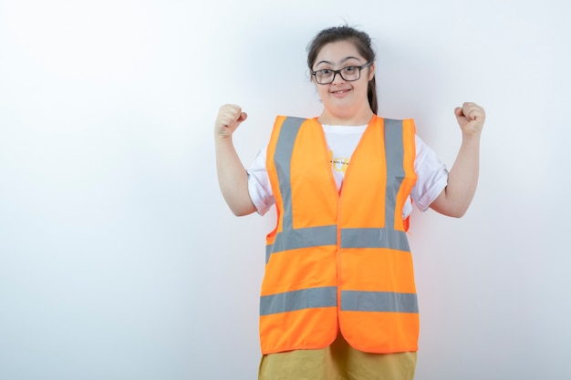 Young female engineer in glasses showing her fists on white wall
