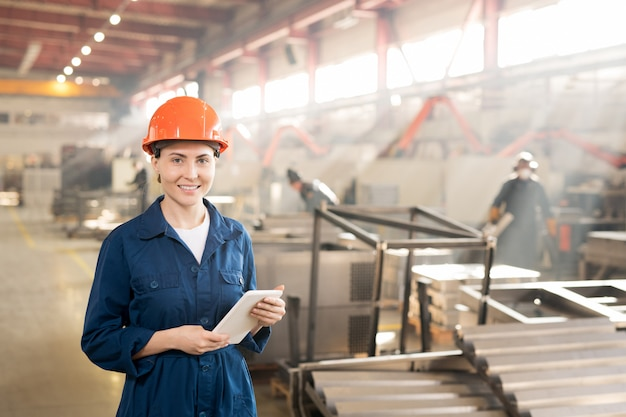 Young female engineer in helmet and blue overalls using modern gadget while working in factory
