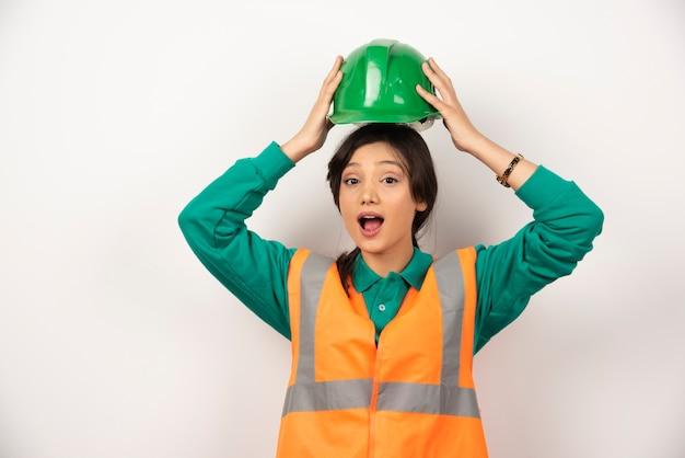 Giovane assistente tecnico femminile che tiene un casco su priorità bassa bianca. foto di alta qualità