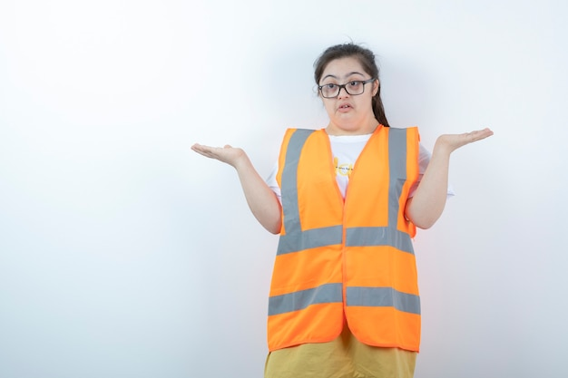 白い壁にオープンスペースを保持している眼鏡の若い女性エンジニア