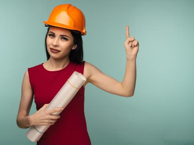 도면과 주황색 헬멧에 젊은 여성 엔지니어 포인트 손가락에 고립 된 파란색 배경-이미지