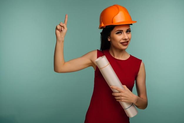 도면과 주황색 헬멧에 젊은 여성 엔지니어가 파란색에 고립 된 손가락을 가리 킵니다.