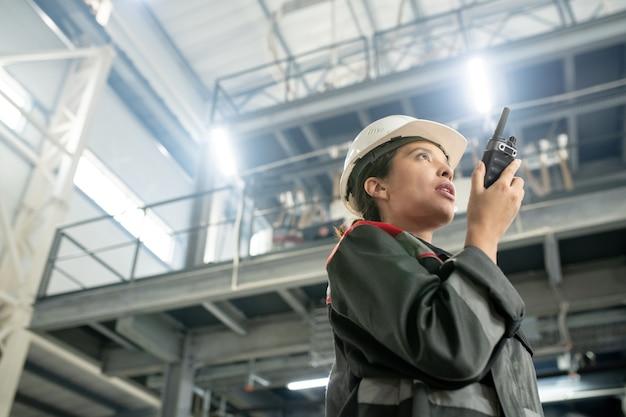현대 공장의 대형 작업장에 서 있는 동안 워키토키를 사용하여 보호용 헬멧과 작업복을 입은 젊은 여성 엔지니어