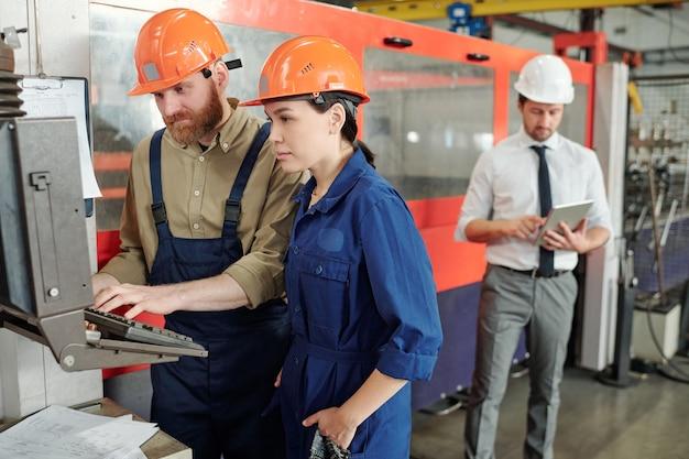 彼女の同僚が近くに立って入力してモニターを見ている若い女性エンジニア