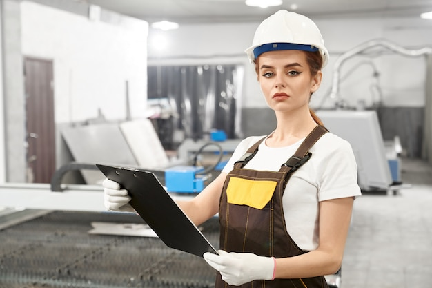 Young female engineer posing while working on metal factory