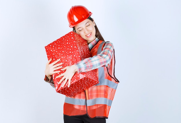 Il giovane ingegnere femminile in casco rosso abbraccia il contenitore di regalo.