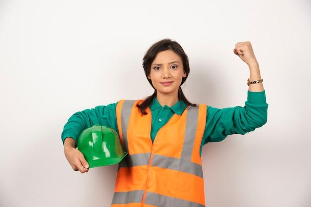 Молодая женщина-инженер показывает мышцы и держит шлем на белом фоне