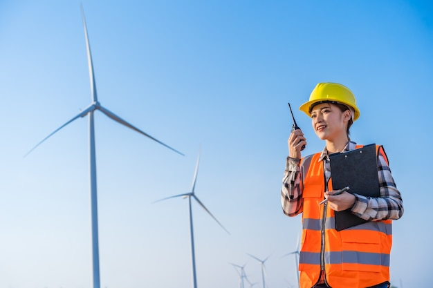 Young female engineer using walkie talkie to checking system against wind turbine farm