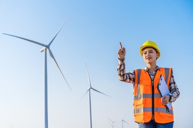 Young female engineer working  against wind turbine farm