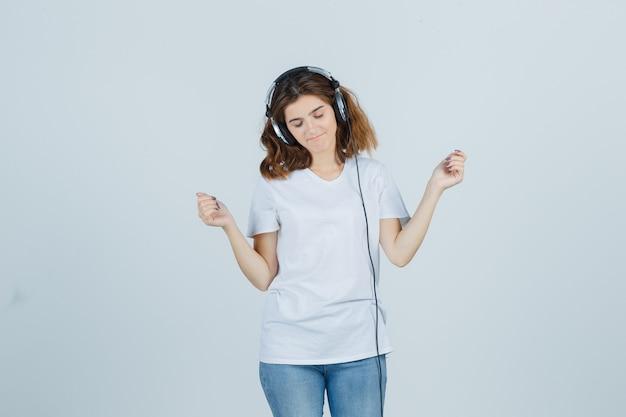 白いtシャツ、ジーンズ、陽気に見えるヘッドフォンで音楽を楽しんでいる若い女性。正面図。