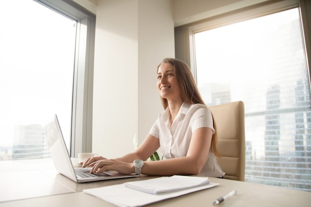 Young female entrepreneur feels happy at workplace