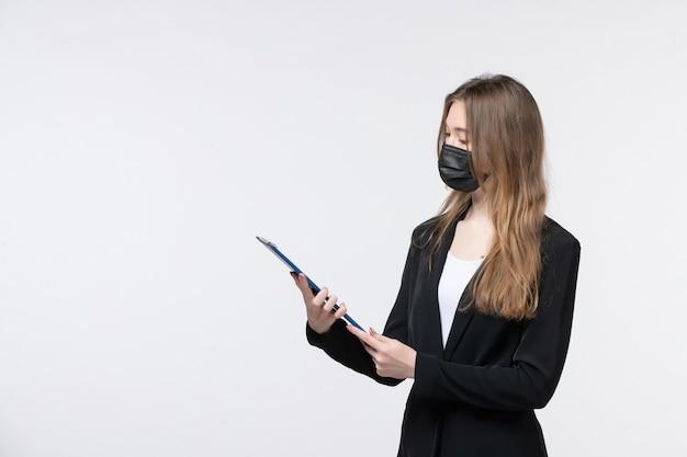 의료용 마스크를 쓰고 흰 벽에 있는 문서를 보고 있는 정장을 입은 젊은 여성 기업가
