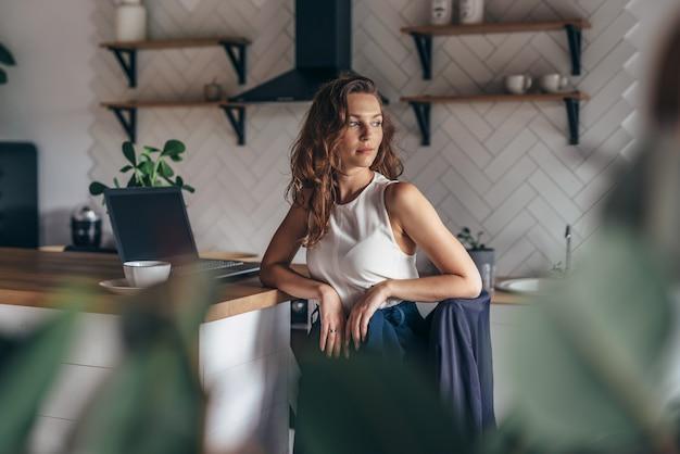 若い女性起業家は台所のテーブルに座っています。
