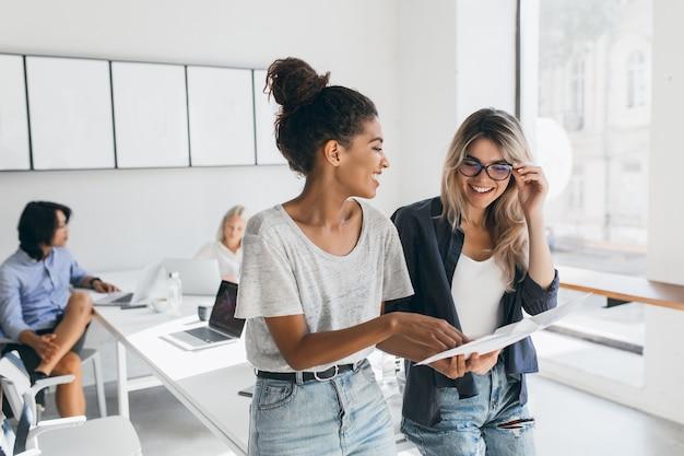 若い女性幹部が眼鏡と笑顔で金髪の従業員に新しい戦略を説明します。オフィスでプロジェクトに取り組んでいて、ラップトップを使用している多文化集団の屋内の肖像画。