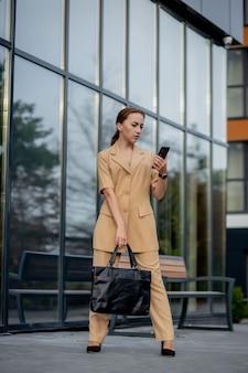 젊은 여성 임원 서 사무실 휴대 전화에 대 한 얘기 건물 밖에 서. caucacian 사업가 본사 건물에 서있는 동안 전화를 만들기.