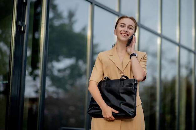젊은 여성 임원 서 외부 사무실 건물 휴대 전화에 대 한 얘기