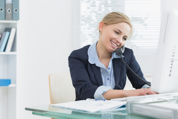 Young female executive using landline phone and computer at desk in office