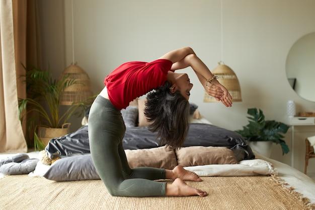 Молодая женщина занимается утром дома, прогибает спину, выполняет вариации устрасаны