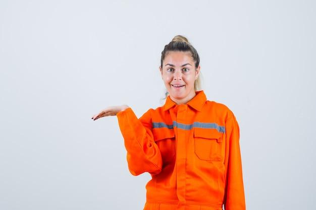 労働者の制服を着た開いた手のひらで手を脇に伸ばして喜んでいる若い女性。正面図。