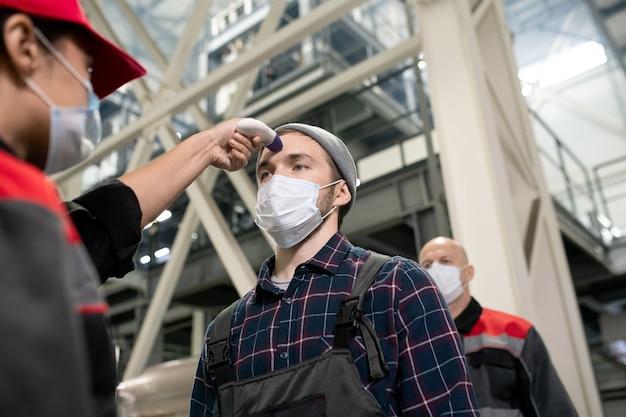Молодая работница фабрики в защитной маске измеряет температуру тела одного из инженеров на фоне огромного строительства