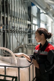 가공되지 않은 플라스틱 알갱이를 원료가 담긴 거대한 용기 위에 들고 있는 젊은 여성 공장 노동자 또는 품질 관리 관리자