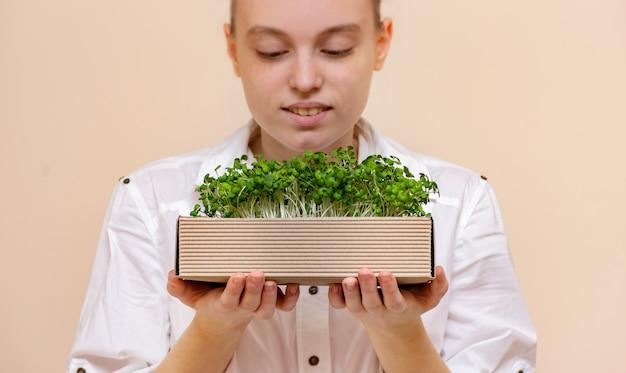 マスタードもやしの有機マイクログラムで作られたエコボックスを保持している若い女性農家。成長するもやし。有機製品。女性の顔にぼやけた焦点。