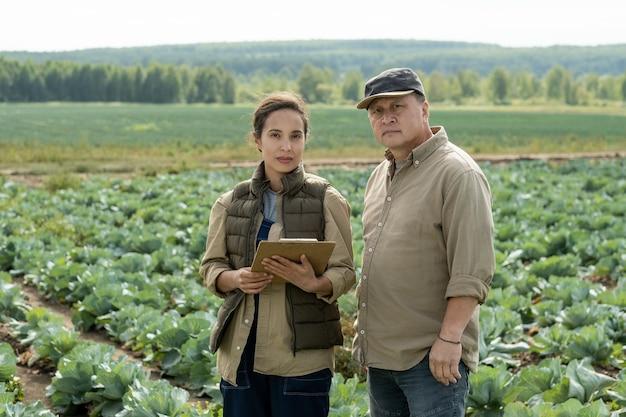Молодая женщина-фермер с документом, стоящим у зрелого мужчины