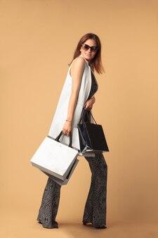 Молодая модница с сумками, изолированными на коричневом фоне