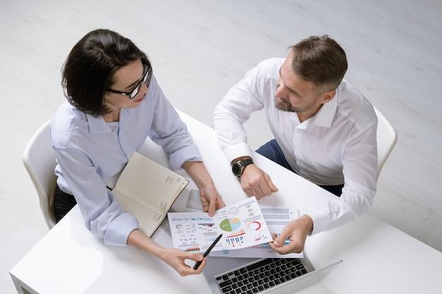 Молодой финансист и ее коллега обсуждают финансовые документы на рабочем совещании, сидя за столом
