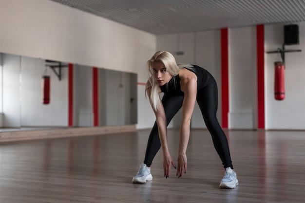 Молодая женщина-инструктор по фитнесу делает упражнения в стильной черной одежде в спортивном классе
