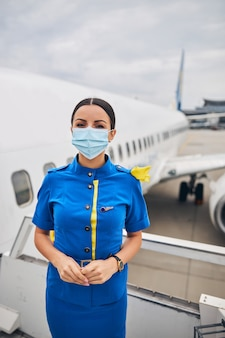 Young female flight attendant staring in front of her