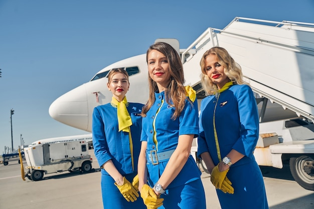 Young female flight attendants in uniforms standing in front of an airplane