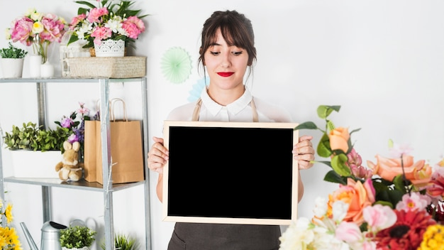Young female florist holding blank slate in floral shop