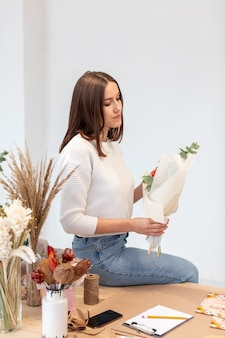 Young female florist sitting sideways with flowers