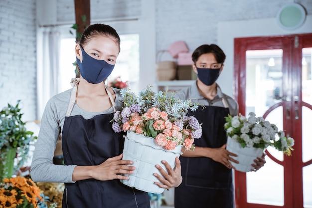 エプロンとフェイスマスクを身に着けている若い女性の花屋は、カメラを見て笑顔のバケツの花を保持しています