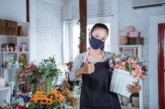 エプロンとフェイスマスクを身に着けている若い女性の花屋は、カメラを見て笑顔のバケツの花を保持している親指を示しています