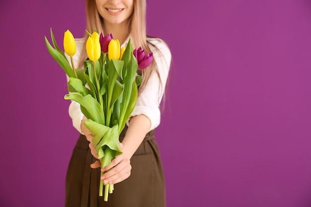 色の背景に花束を持つ若い女性の花屋